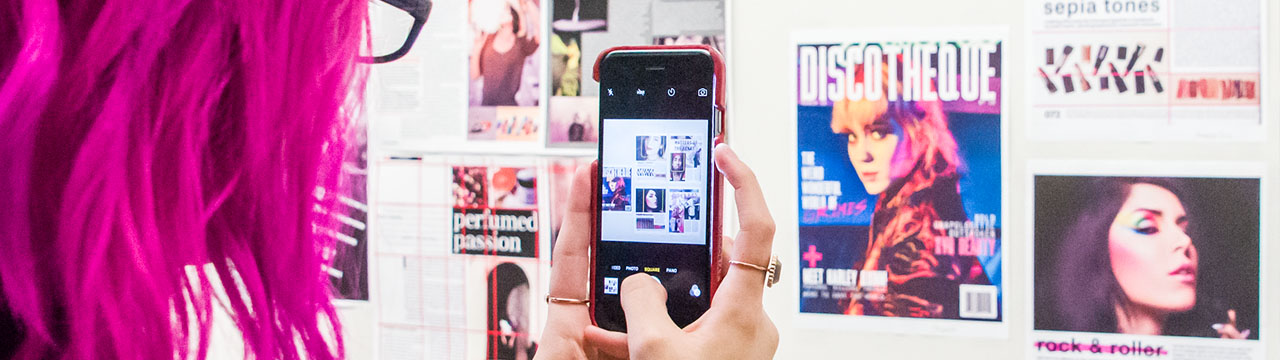 Student snaps a picture of a design display with her phone