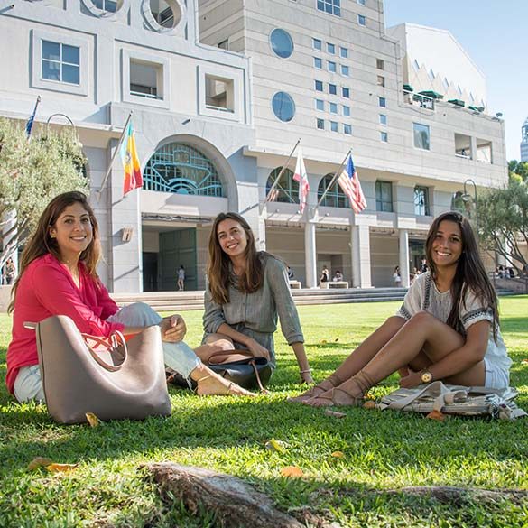 Three students enjoy the sun in Hope Park in front of FIDM Los Angeles