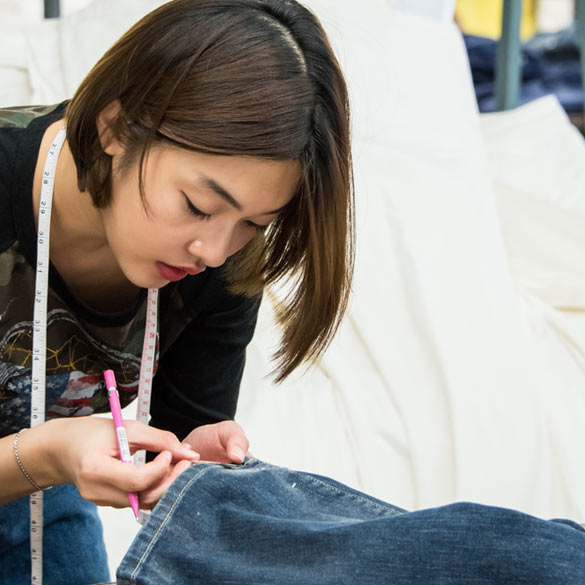 Student sewing denim garment