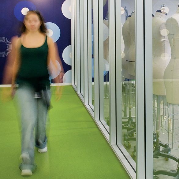 Student walking down a green hallway outside of a fashion design classroom