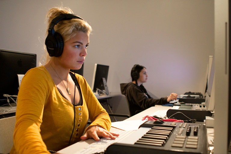 A student wearing headphones scores her video at an audio workstation