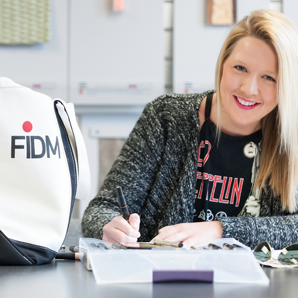 Student working at table with FIDM tote next to them
