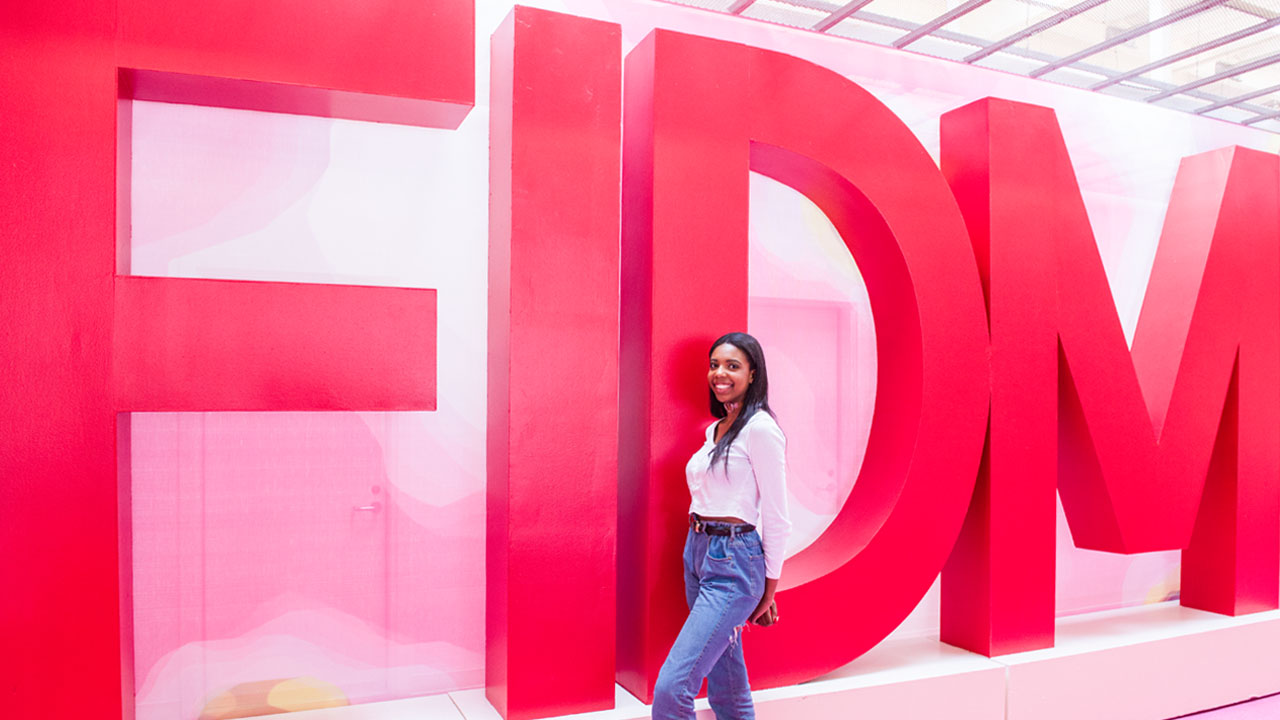 student in front of FIDM sign